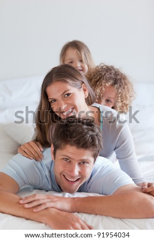 Portrait of a happy family lying on each other in a bedroom