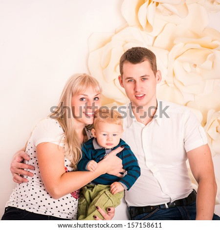 Portrait of a happy family: mother, father and a baby - stock photo