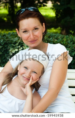 Portrait of a happy family. Mum with a daughter in park - stock photo