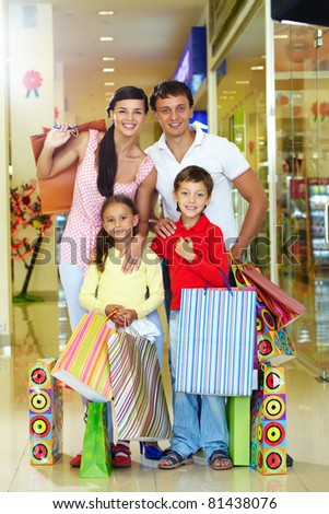Portrait of a happy family of four in store looking at camera and smiling - stock photo