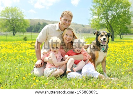 Portrait of a happy family of four people, including mother, father, young child, and baby sitting outside with their German Shepherd mix dog on a Spring day. - stock photo