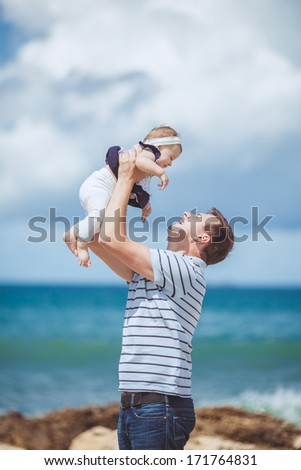 portrait of a Happy family of man and child having fun by the blue sea in summertime