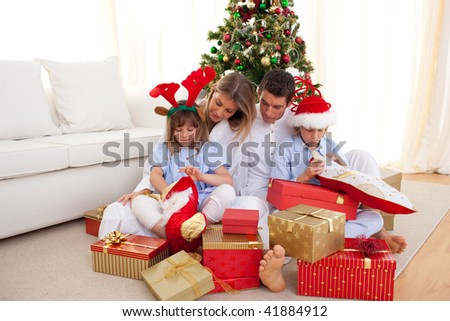 Portrait of a happy family opening gifts at Christams time - stock photo