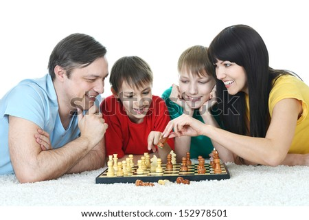 portrait of a happy family playing chess at home - stock photo
