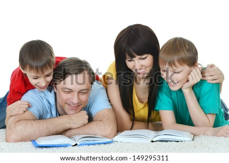 portrait of a happy family reading a book on the floor - stock photo