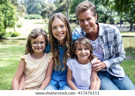 Portrait of a happy family sitting in the park - stock photo