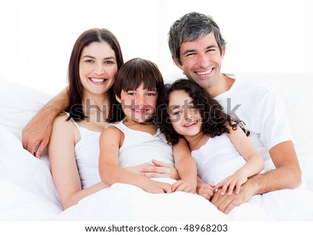 Portrait of a happy family sitting on a bed at home - stock photo