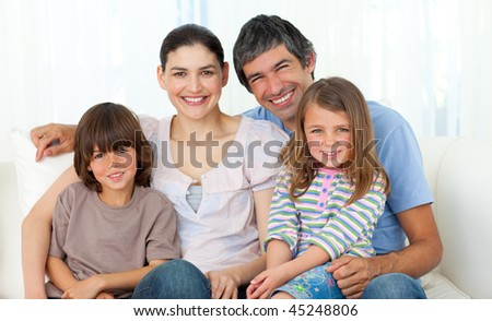 Portrait of a happy family sitting on a sofa - stock photo