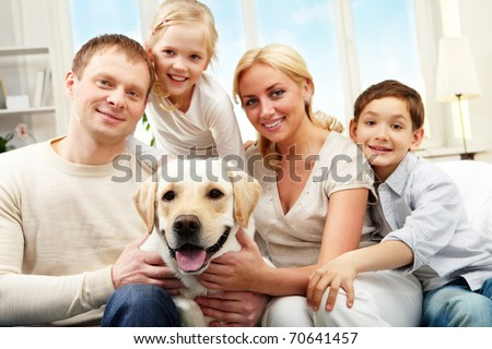 Portrait of a happy family sitting on sofa with a dog, looking at camera and smiling