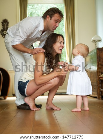 Portrait of a happy family smiling at baby standing at home - stock photo
