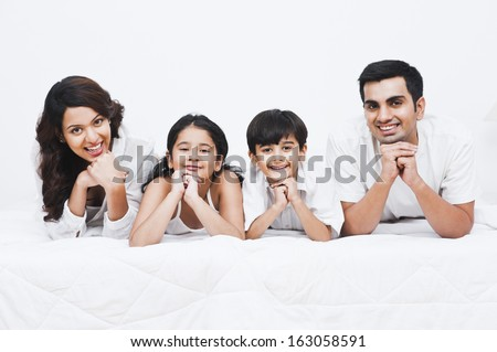 Portrait of a happy family smiling on the bed - stock photo