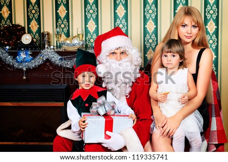 Portrait of a happy family spending Christmas time with Santa Claus at home. - stock photo