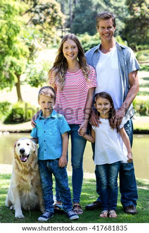 Portrait of a happy family standing in the park with their dog - stock photo