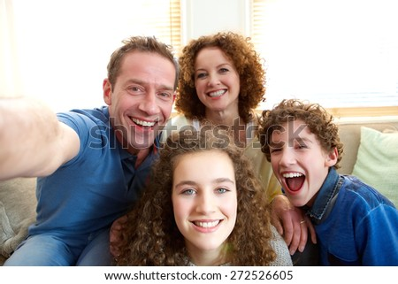 Portrait of a happy family taking a selfie at home - stock photo