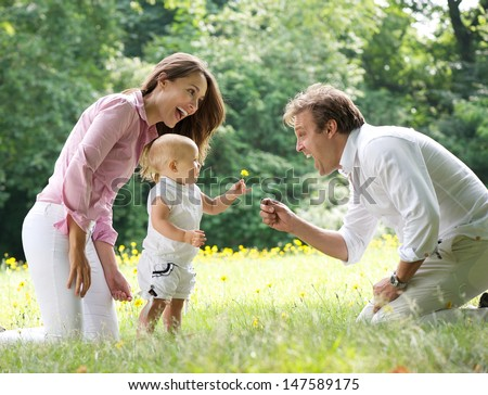 Portrait of a happy family with child giving flower to father int he park - stock photo