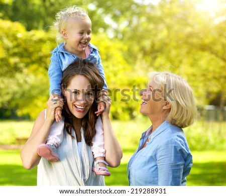 Portrait of a happy family with smiling mother and grandmother - stock photo
