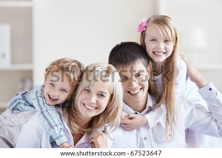 Portrait of a happy family with two children at home - stock photo