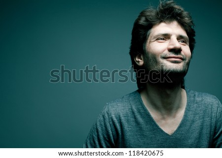 Portrait of a happy fashionable handsome man in gray sweater (pullover) over blue (green) background with a friendly smile. Close-up. Copy-space. studio shot - stock photo