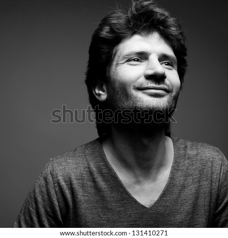 Portrait of a happy fashionable handsome man in gray sweater (pullover) over gray background with a friendly smile. Perfect hair. Close up. Copy-space. Black and white (monochrome) studio shot - stock photo