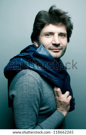 Portrait of a happy fashionable handsome man in gray sweater (pullover) with blue leather jacket on his shoulders over blue (green) background with a friendly smile. studio shot - stock photo