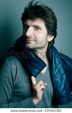 Portrait of a happy fashionable handsome man in gray sweater (pullover) with blue leather jacket on his shoulders posing over blue (green) background with a friendly smile. Studio shot - stock photo