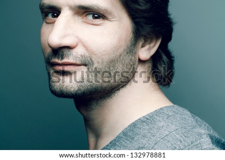 Portrait of a happy fashionable handsome mature man in gray sweater (pullover) posing over dark blue (green) background with a friendly smile. Perfect hair and skin. Close up. Studio shot - stock photo