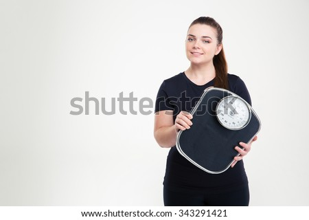 Portrait of a happy fat woman holding weighing machine isolated on a white background - stock photo