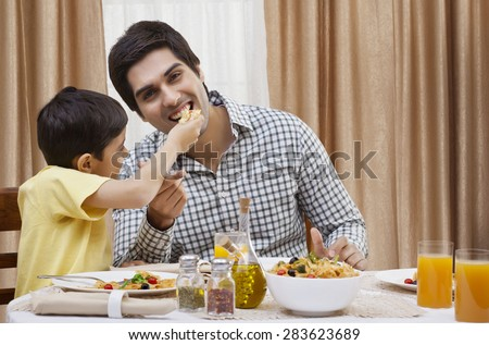 Portrait of a happy father being fed a piece of pizza by his son - stock photo