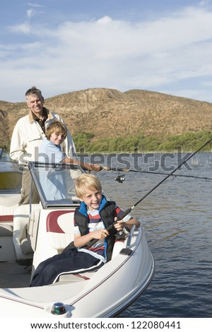 Portrait of a happy father with sons fishing in boat on lake - stock photo