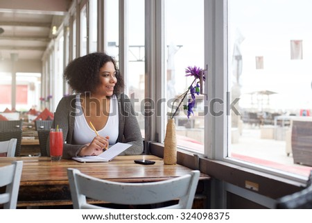 Portrait of a happy female college student sitting at restaurant with note pad and pencil - stock photo