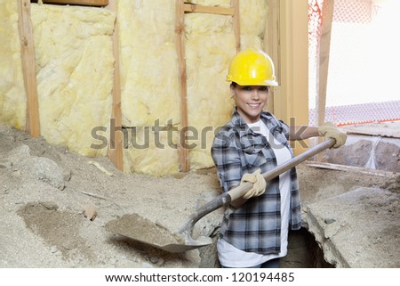 Portrait of a happy female contractor digging sand at construction site - stock photo