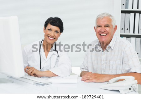 Portrait of a happy female doctor with male patient at medical office - stock photo