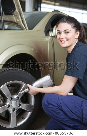 Portrait of a happy female mechanic changing a tire in a shop - stock photo