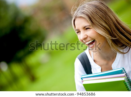 Portrait of a happy female student laughing outdoors - stock photo