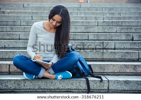 Portrait of a happy female student sitting on the city stairs and writing notes in notepad outdoors