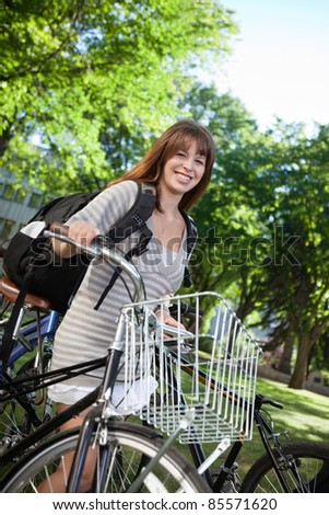 Portrait of a happy female student standing with her bike - stock photo
