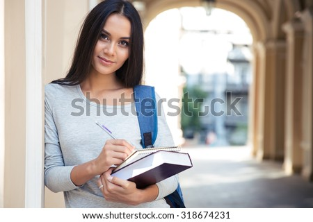Portrait of a happy female student writing notes in notepad and looking at camera outdoors - stock photo