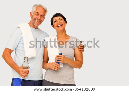 Portrait of a happy fit couple against grey vignette - stock photo