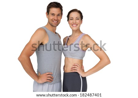 Portrait of a happy fit young couple with hands on hips over white background