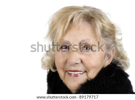 Portrait of a happy friendly senior woman smiling looking at camera and wearing a black fur collar for the cold winter day. - stock photo