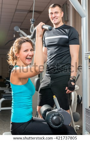 portrait of a happy girl and trainer in the gym - stock photo