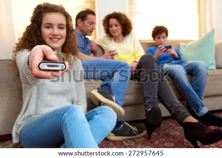 Portrait of a happy girl holding remote control with family in the background - stock photo