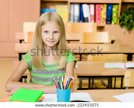 portrait of a happy girl in classroom - stock photo