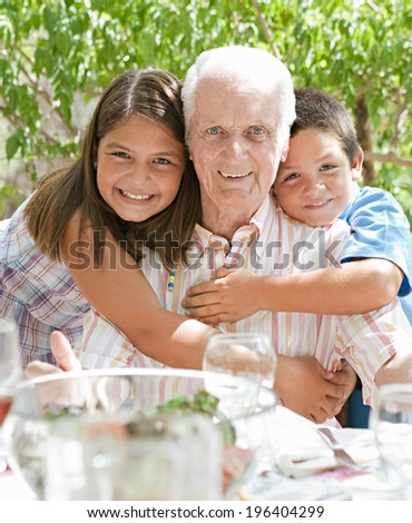 Portrait of a happy grandfather with his joyful grand children hugging him during a sunny summer day on a holiday home green garden while having lunch outdoors. Family relaxing on vacation, lifestyle. - stock photo