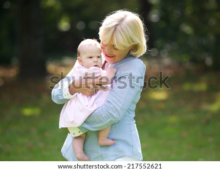 Portrait of a happy grandmother holding cute baby - stock photo