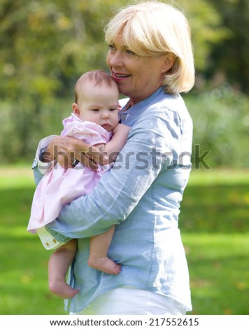 Portrait of a happy grandmother smiling with baby granddaughter  - stock photo