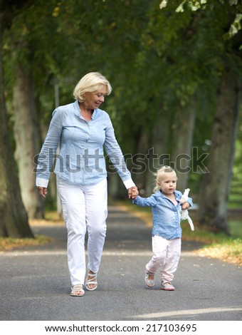Portrait of a happy grandmother walking with baby girl in park - stock photo