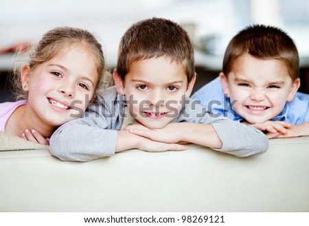 Portrait of a happy group of kids smiling - indoors - stock photo