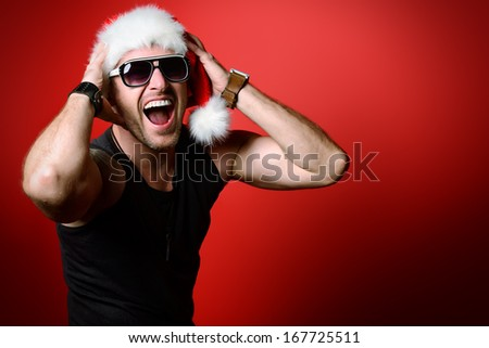 Portrait of a happy handsome brutal man in Christmas hat. Over red background. - stock photo
