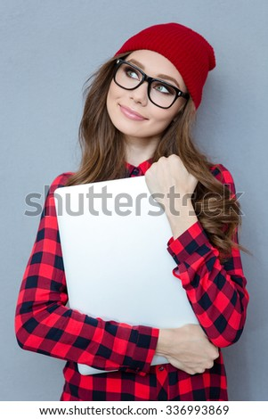 Portrait of a happy hipster woman holding laptop computer and dreaming over gray background - stock photo